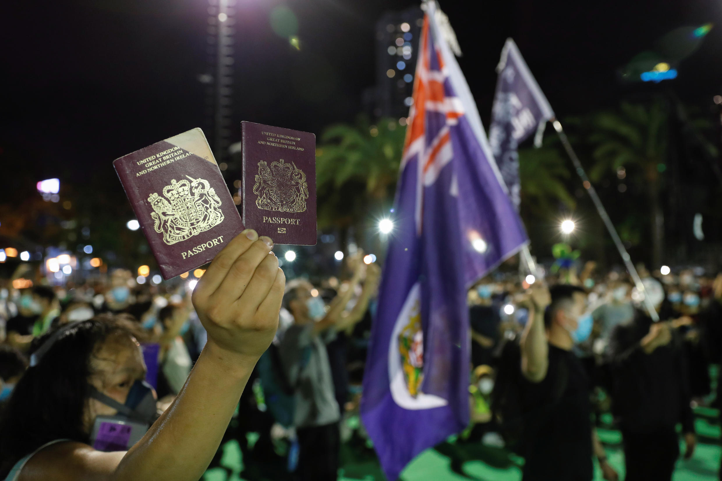 A protester displays his British passport abroad during a demonstration to commemorate the Tiananmen Square Massacre in Hong Kong on June 4, 2020.