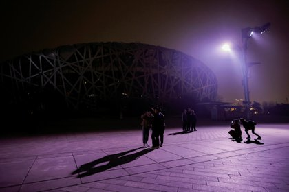 People stand in front of the National Stadium, also known as the Bird's Nest, in Beijing, China