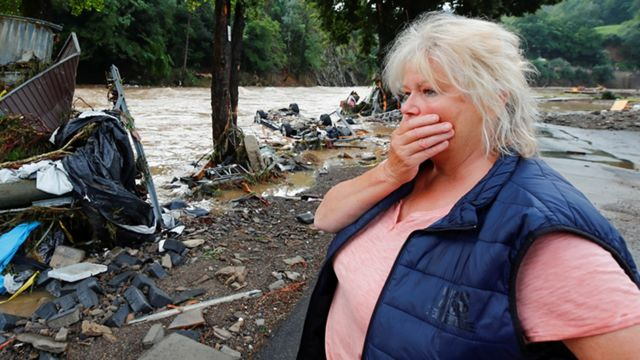 A woman looks at the debris carried by the waters adjacent to the Ahar River.