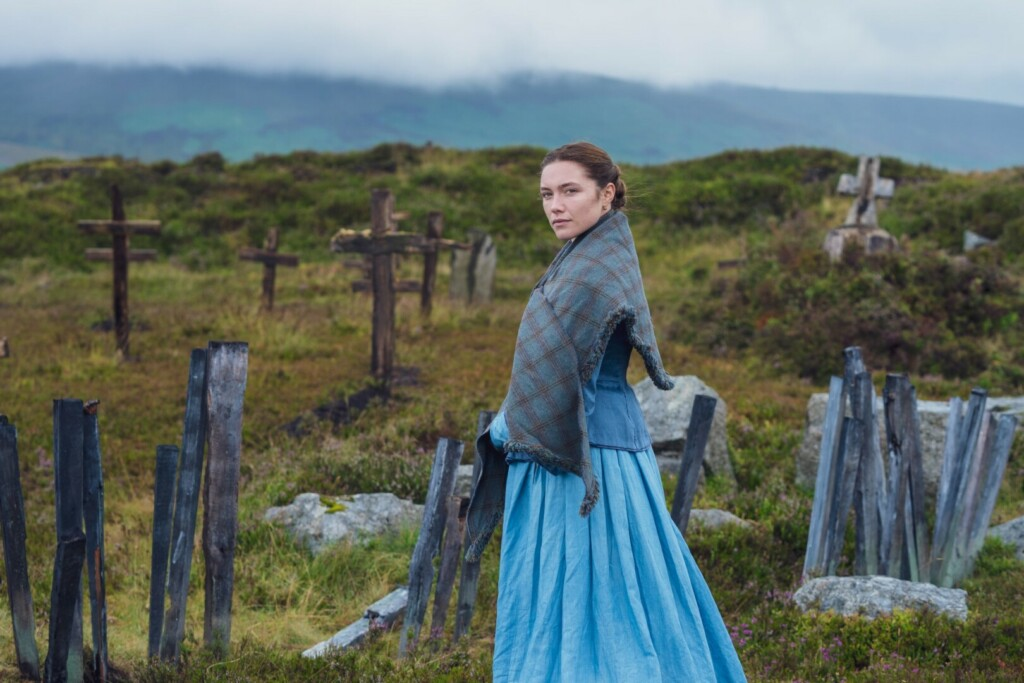 Portrait of actress Florence Pugh featuring 19th century clothing on the set of 'The Wonderland', in a sort of cemetery in the Irish countryside