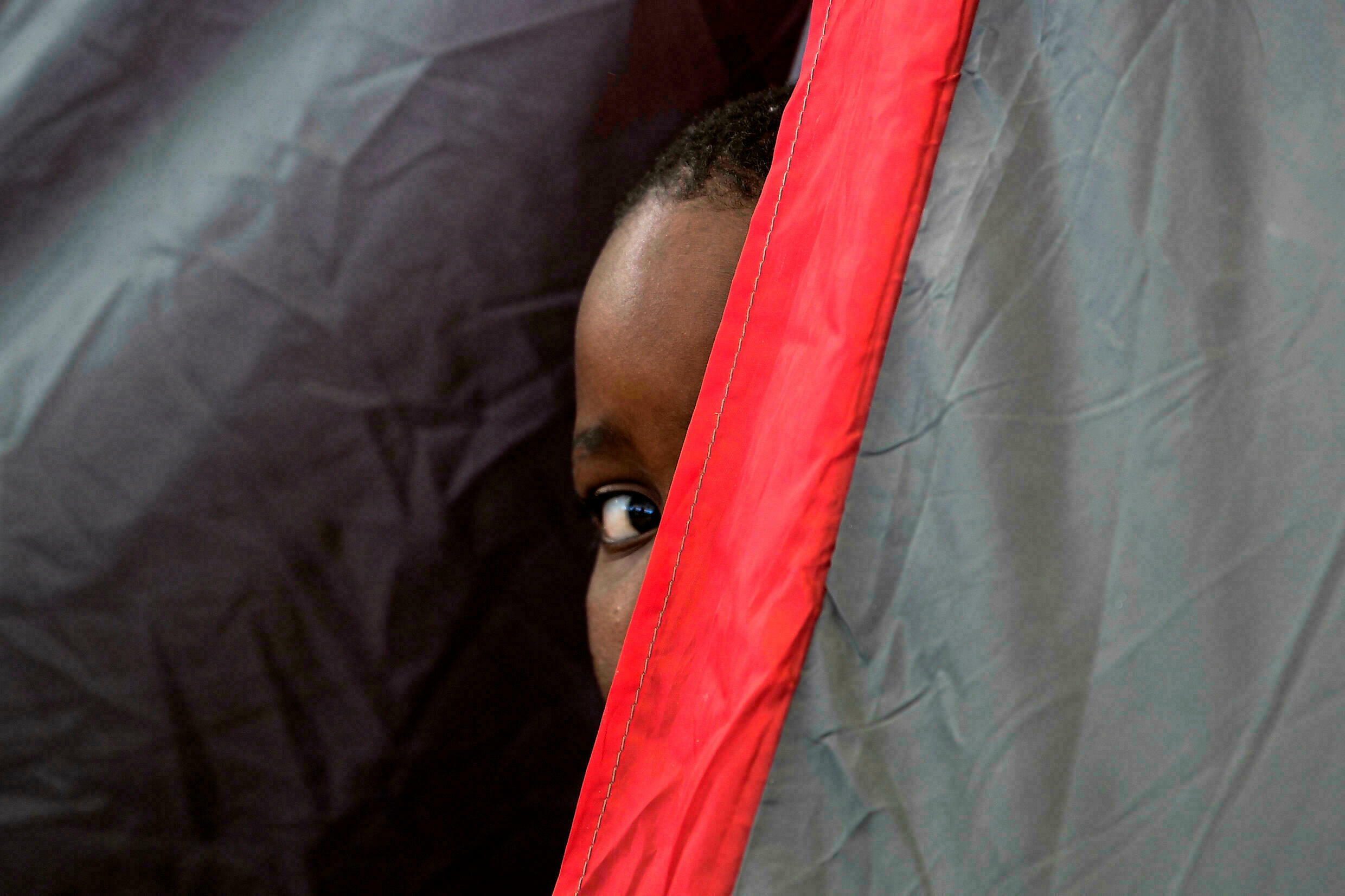 A young Haitian man looks out of a tent in Ciudad Acuña, Mexico, on September 25, 2021